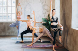 women in activewear adapting yoga poses in a fitness studio